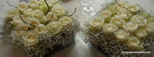 low square table vases of white roses at one level in grid form with gypsophlia collar
