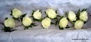 Romantic wedding flowers. Ivory rose buttonholes with foliage
