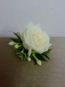 Romantic wedding flowers Ivory rose buttonhole with varigated foliages and stephanotis buds