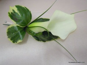 contemporary white calla lily buttonhole with varigated foliages and bear grass