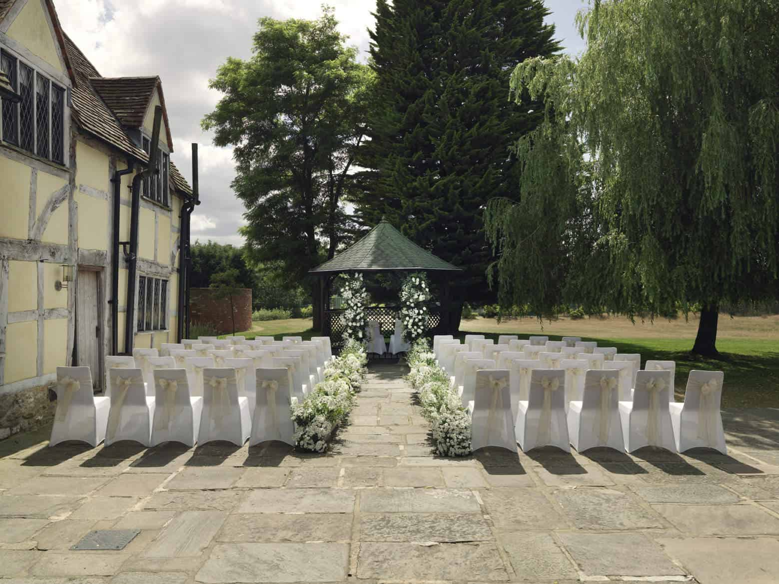 cain manor wedding venue - out door ceremony with white hydrngea plants forming aisle wakway & gazebo arch