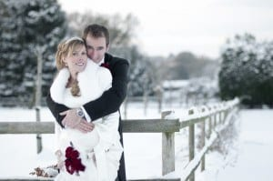 bride and groom snow scene. Bride with red rose bouquert & feather trim